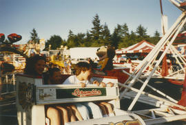 Children and Tillicum ride the scrambler amusement park ride