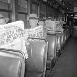 Reading [News Herald in a streetcar]