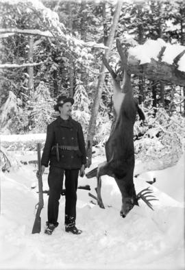 [Man standing next to deer strung up on stick in snow covered forest]