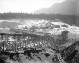 [Coquitlam Dam site covered in snow, showing trestle supported flume and construction camp]