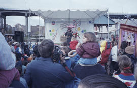Unidentified man in costume speaking into microphone on Chevron stage