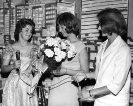 Young woman receiving flowers at unidentified P.N.E. event