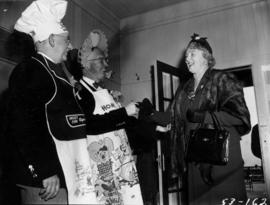 P.N.E. President J.S.C. Moffitt in maid costume greeting woman at tea party