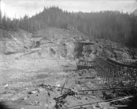 [Partially constructed Coquitlam Dam, showing trestle supported flume and hydraulic monitors]