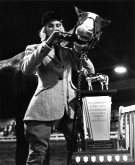 "Winning rider of the T.N. ""Nick"" Henderson trophy in 1964 P.N.E. Horse Show pouring col..."