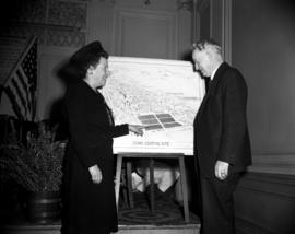 [Man and woman looking at a drawing of a proposed civic centre site]