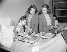 [Women from the Junior League showing toys to a young girl]