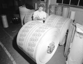 [Woman checking rolls of paper for] Pacific Mills