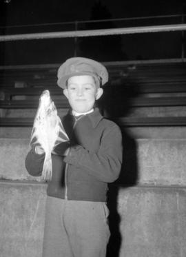 [Young boy holding a fish]