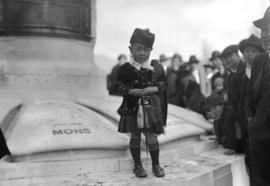 [Japanese child dressed in Scottish costume at war memorial]