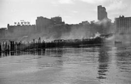 [The smoldering ruins of Pier D from the water]