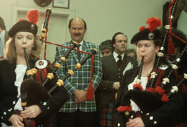 Mike Harcourt wearing Centennial tartan with bagpipers in the foreground