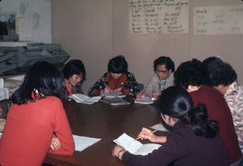 Adult students going over English-language exercises