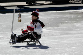 A young boy carries the Paralympic lantern via sledge hockey at Community Celebration in Toronto,...