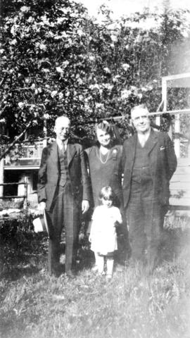 [L.D. Taylor and unidentified man, woman and girl standing in yard]