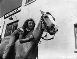 Girl riding horse by Livestock Judging building