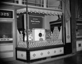 [Spork canned meat and Bendix washing machine display in a store window]