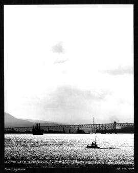 Morning shine [view of Second Narrows Bridge with freighter and small boat in the foreground]