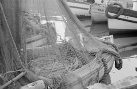 [Fishing nets draped over boat at dock]