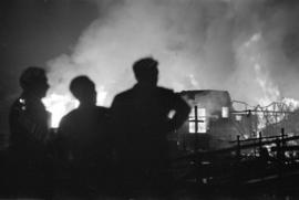 Silhouettes of three men watching the fire burning Denman Arena
