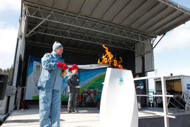 Torchbearer 22 lighting the cauldron on the Riley Park stage