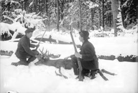 [Man and teenage boy posing with deer laid out in snow]
