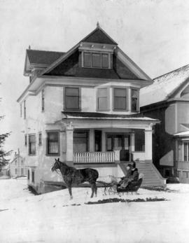 [Mr. and Mrs. J.P. Forbes in a horse-drawn sleigh in front of their house at 467 West 10th Avenue]