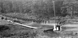 [Soldiers marching along a road with a work party of German prisoners of war]