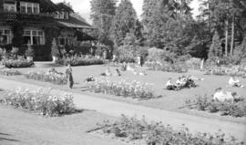 [People seated on lawn by flower beds in front of the Stanley Park Pavillion]