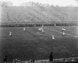 [A football match in a crowded stadium]
