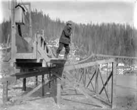 [Man on sluicing flume for construction of Coquitlam Dam]