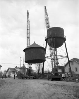 [Cranes lifting a cap to the top of a water tower]