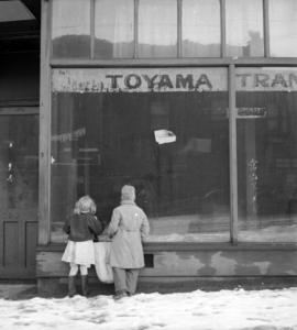 [Children looking in the window of a Japanese store, closed after the relocation of Japanese nati...