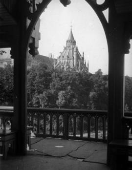 [View of the roof of the Parliamentary Library through an arch]