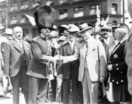 Lieutenant R.G. Evans, director of the H.M. Coldstream Guards band, shaking hands with dignitary