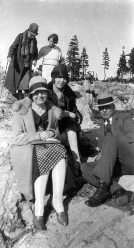 [L.D. Taylor sitting on rocks with two unidentified women]