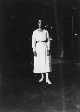 [Woman standing on lawn in white dress]