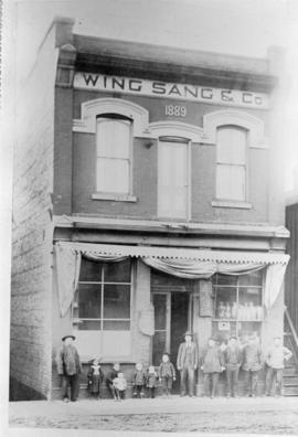 Yip Sang with children and unidentified men in front of Wing Sang Company building at 51 East Pen...
