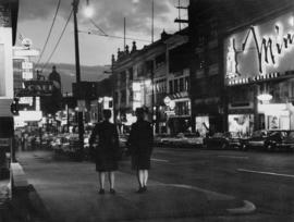 [Two female police officers walking down 100 block E. Pender Street in evening]