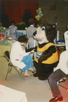 Tillicum gets his blood pressure tested beside St. Paul's Hospital display table