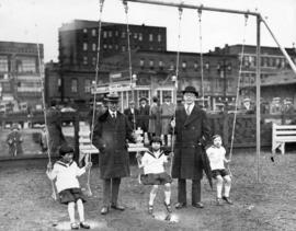 [Mayor L.D. Taylor with children and unidentified man at opening of children's playground at Carr...