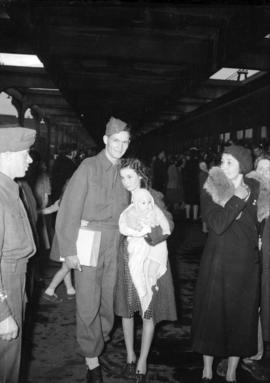 [Soldier leaving for the war with wife and child at the train station]