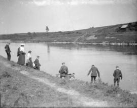 [Unidentified group studying plants along a river]