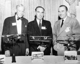 [Three members of The Early Bird Club in front of model airplanes]