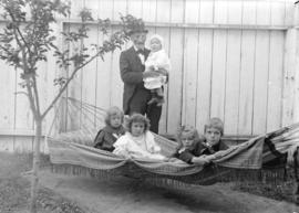 [Older man and five young children at hammock outside Robert Scott residence, southwest corner of...