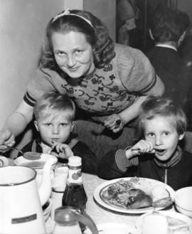 [Hungarian refugees have a meal in the Immigration Building at the airport]
