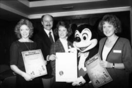 Group holding proclamation with Mickey Mouse