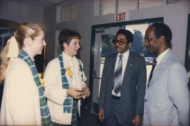 Centennial staff members talking with two unidentified men