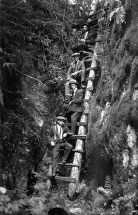 [Four photographers, including James Crookall, posed on a ladder made from rough logs]