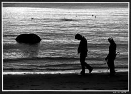 Man and woman walking along the beach
